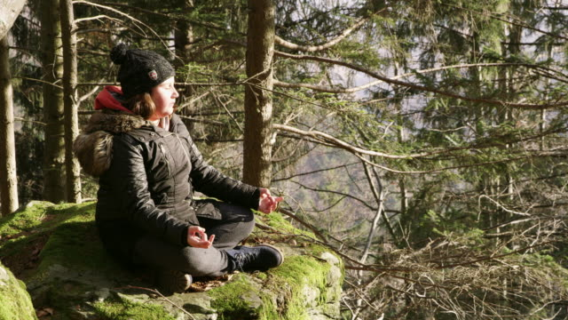 4K Serene girl meditating on rock in forest, real time