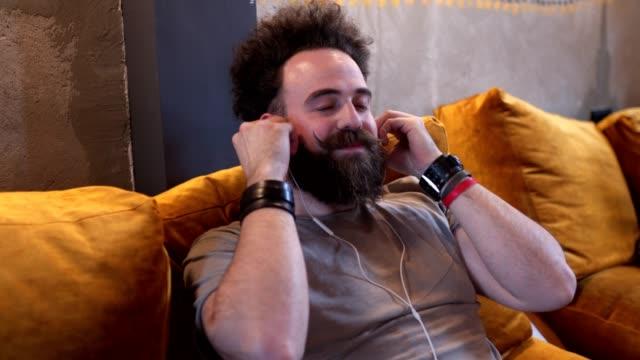 serene hipster enjoying music on headphones at a cafe - occhi chiusi video stock e b–roll