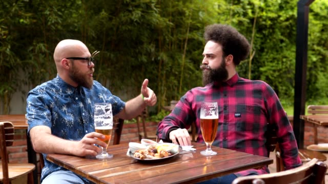 serene hipsters having a drink and a chat at a local cafe - only men stock videos & royalty-free footage