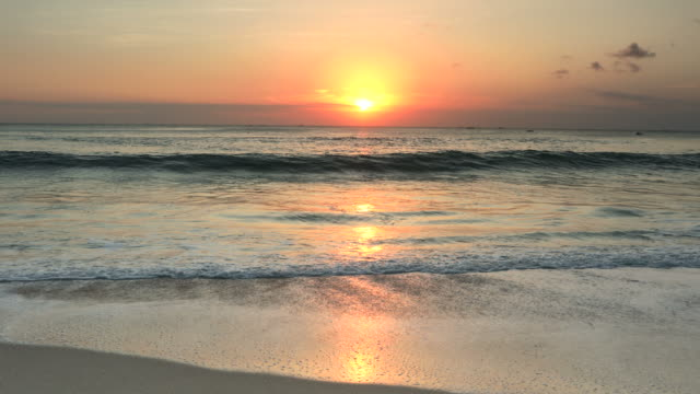 serene sunset on a tropical beach with breaking waves - riva dell'acqua video stock e b–roll