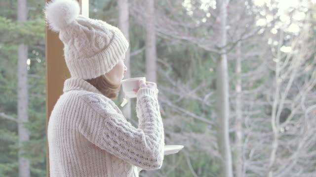 4K Serene woman drinking tea on winter patio in forest, slow motion