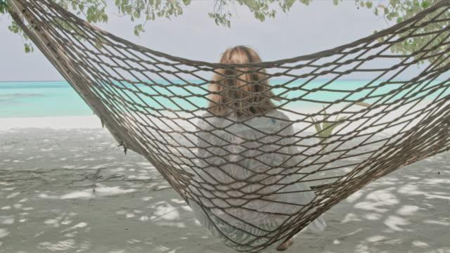 ms heitere frau in hängematte am idyllischen tropischen ocean beach, malediven - blondes haar stock-videos und b-roll-filmmaterial