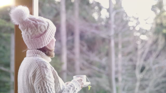 4K Serene woman in knit hat drinking tea on winter patio, real time