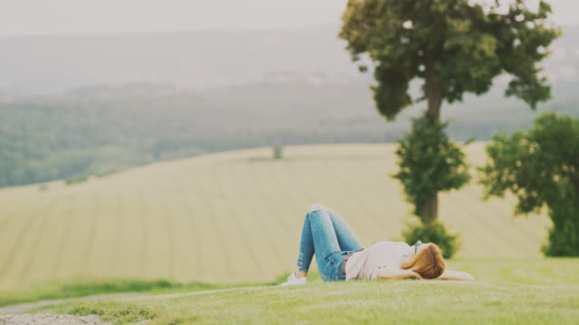 ms serene woman laying in tranquil, idyllic rural field, goricko nature park, gard, slovenia - lying down stock videos & royalty-free footage