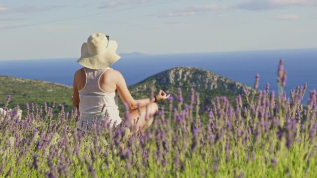 MS Serene woman meditating among lavender on sunny hilltop with scenic ocean view,Hvar,Croatia