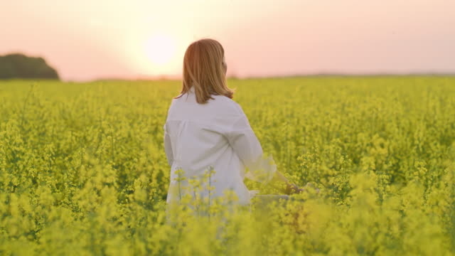 ms serene woman meditating in tranquil,rural oilseed rape field - zen like stock videos & royalty-free footage