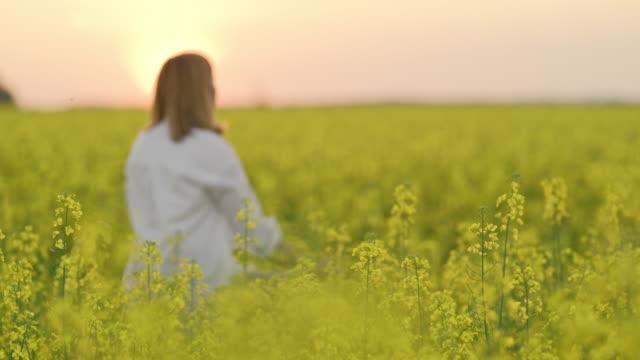 ms serene woman meditating in tranquil,rural oilseed rape field - rack focus stock videos & royalty-free footage