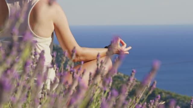 ms slow motion  serene woman meditating with hand in gyan mudra behind lavender,overlooking sunny ocean - mediterranean sea stock videos & royalty-free footage
