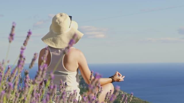 vidéos et rushes de femme sereine ms slow motion méditer avec les mains en gyan mudra derrière lavande, avec vue sur océan ensoleillé - chapeau