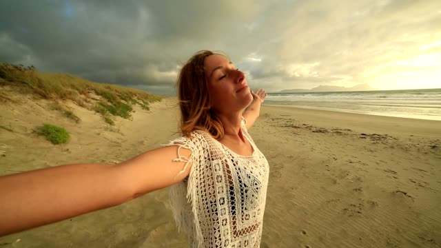 serene woman relaxes on beach at sunset - baia delle isole nuova zelanda video stock e b–roll