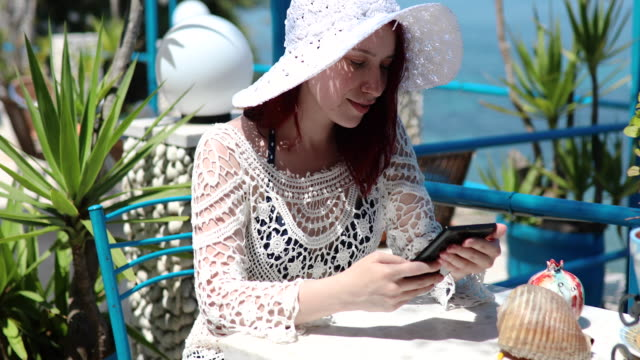 serene woman relaxing at the beach coffee shop and checking her social media on tablet computer - sun hat stock videos & royalty-free footage