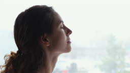 Serene young woman breathing fresh clean air with eyes closed