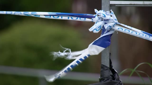 decontamination expected to take months england wiltshire salisbury ext close shot blue police cordon tape tied to fence blue police tape blowing in... - ロープ仕切り点の映像素材/bロール