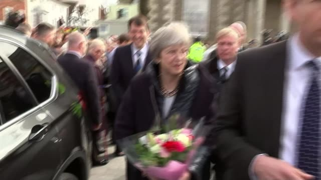 May warns Russia / Allies support the UK Theresa May holding flowers as along past public