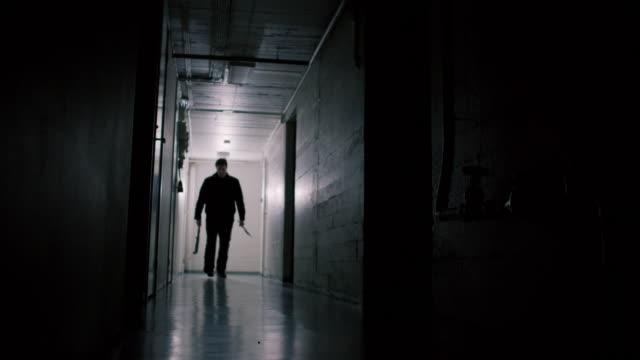 stockvideo's en b-roll-footage met serial killer walking down scary hallway - bijl