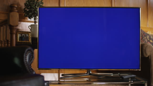 Series of camera dollies past a leather chair to reveal a large flat screen television with a blue screen in a living room.