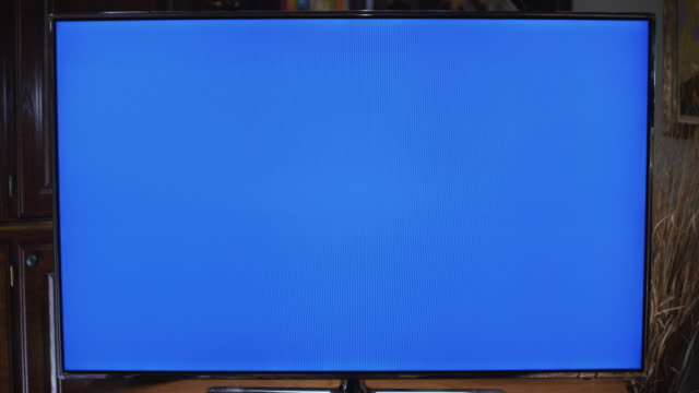 series of camera dollies toward and away from large screen tv with blue screen for picture replacement. - zoom in stock videos & royalty-free footage