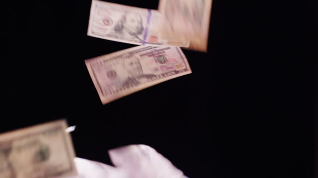a series of currency and large denominations of paper money (dollar bills) float and flip past camera over a black background. - banknote stock videos and b-roll footage