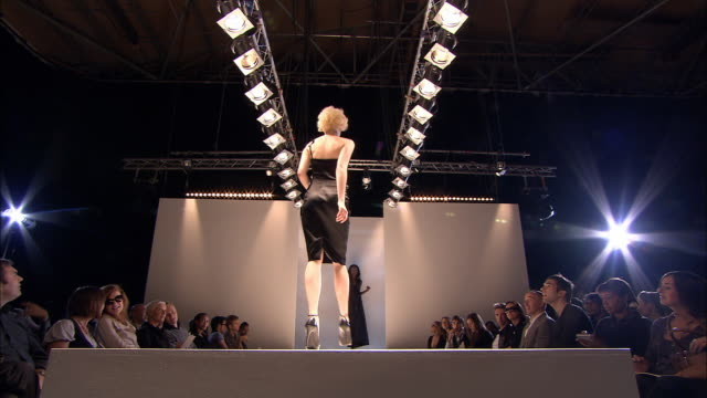 LA WS Series of male and female models walking on catwalk in front of audience at fashion show/ London, England