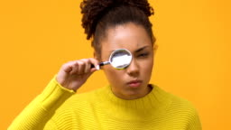 Serious african woman looking through magnifying glass, female detective, search