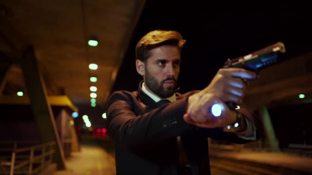stockvideo's en b-roll-footage met de ernstige agent zoekt een misdadiger met zijn een kanon en zaklamp in zijn hand - pursuit concept