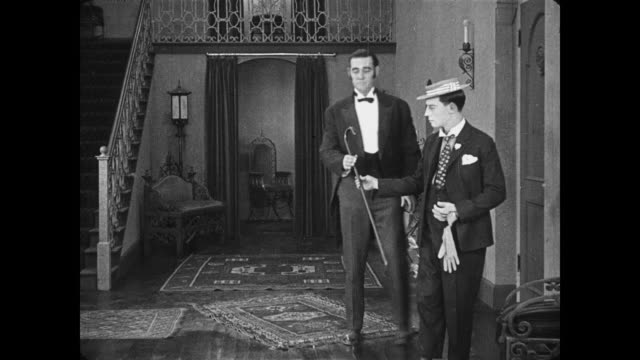 1922 Serious and well dressed man (Buster Keaton) hands hat and gloves to servant before slipping on rug in foyer