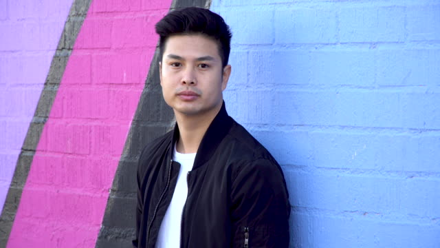 serious asian young adult standing against a building wall. - brick wall stock videos & royalty-free footage