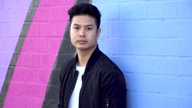 schweren asiatischen junger erwachsener stehend gegen eine wand des gebäudes. - ziegelmauer stock-videos und b-roll-filmmaterial