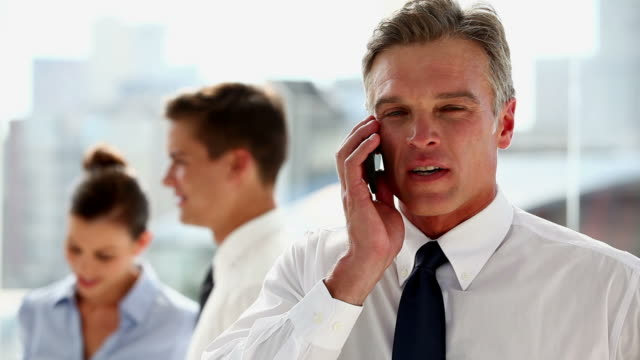 stockvideo's en b-roll-footage met serious businessman having a phone discussion - overhemd en stropdas