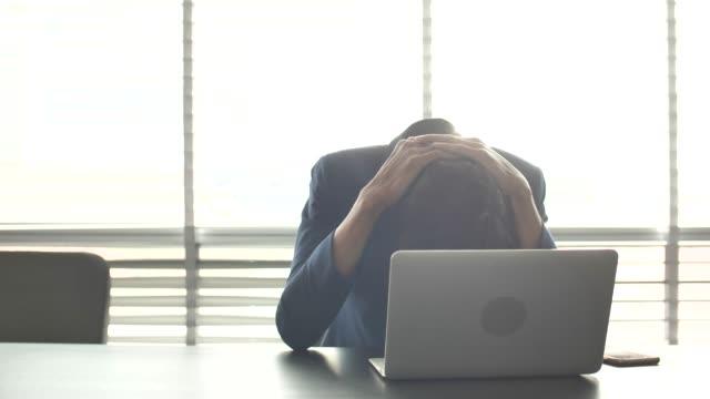 ラップトップで作業する深刻なビジネスマン、仕事の疲れ