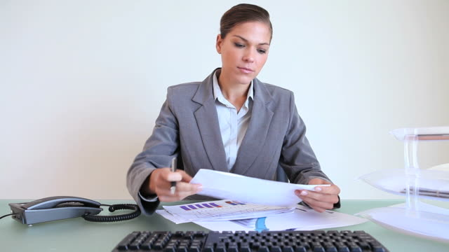 stockvideo's en b-roll-footage met serious businesswoman holding charts - compleet pak