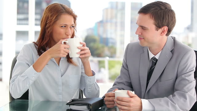 Serious colleagues talking together while drinking coffee