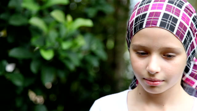 Serious expression on female cancer survivor with headscarf
