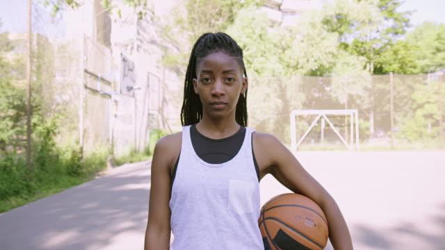 vidéos et rushes de athlète féminin sérieux avec le basket-ball à la cour - rôle dans le sport
