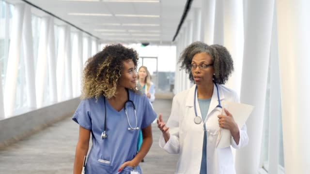 serious female doctor talks with female nurse - elevated walkway stock videos & royalty-free footage