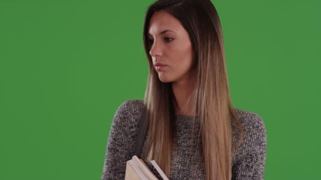 Serious female millennial university student holding books  on greenscreen