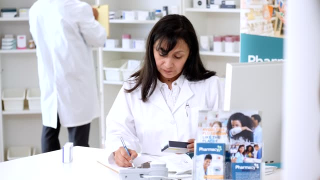 serious female pharmacist works on customer's prescription - doctor multitasking stock videos & royalty-free footage