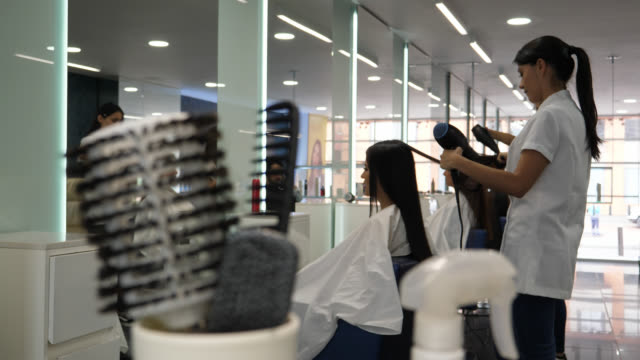 serious hairdresser drying a customer's hair with a hairdryer and brush - hairdresser stock videos & royalty-free footage