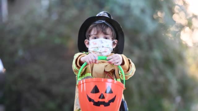 ernster kleiner junge trägt ein halloween-feuerwehrkostüm und eine schützende gesichtsmaske, die auf die kamera schaut, die einen jack o lantern eimer hält - halloween stock-videos und b-roll-filmmaterial