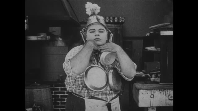 vidéos et rushes de 1918 serious looking chef (fatty arbuckle) wearing pots and pans dances up close and personal with camera - 1918