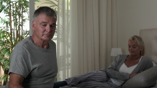 stockvideo's en b-roll-footage met serious looking couple in bedroom - dubbel bed