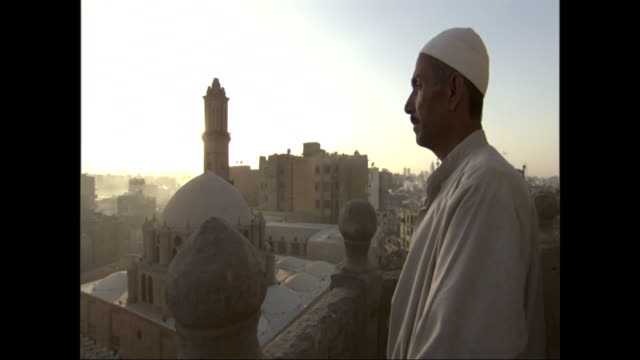 a serious looking man in a tunic stands on a hill overlooking a mosque. - tunic stock videos & royalty-free footage