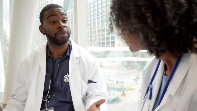 serious male doctor discusses something with colleague - shaking head stock videos & royalty-free footage