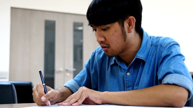 stockvideo's en b-roll-footage met ernstige mannelijke student schrijven in de klas - leesbril
