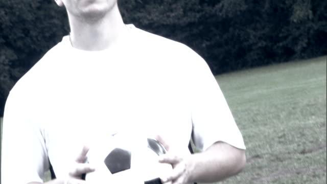 Serious man holding soccer ball