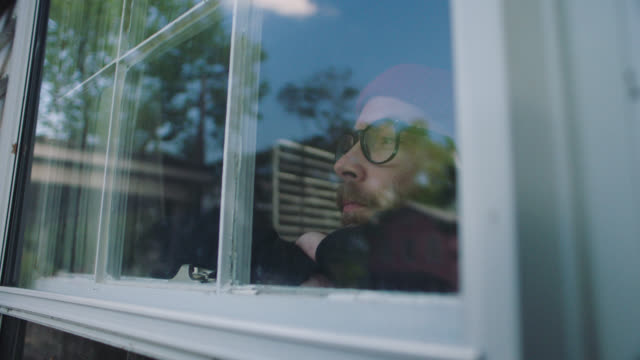 vídeos de stock e filmes b-roll de slo mo. cu of serious man looking out a window. - sério