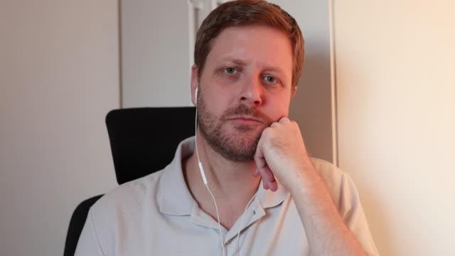 vidéos et rushes de homme sérieux sur un appel vidéo avec des collègues - hot desking