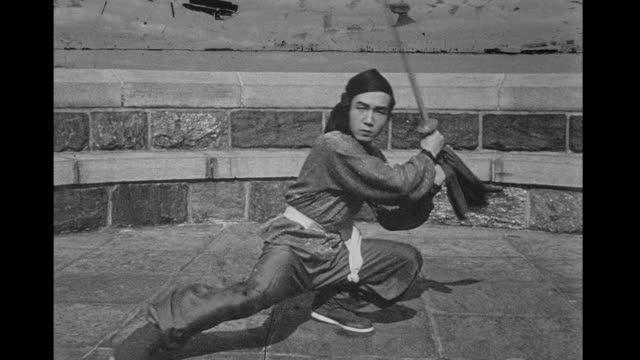 1948 serious man (chao-li chi) performs martial arts sequencing using a sword outside - 1948 stock-videos und b-roll-filmmaterial