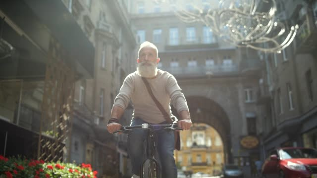 Serious mature guy riding bicycle down street