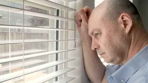 seriös mogen man tittar genom sitt hem fönster - sorgsenhet bildbanksvideor och videomaterial från bakom kulisserna